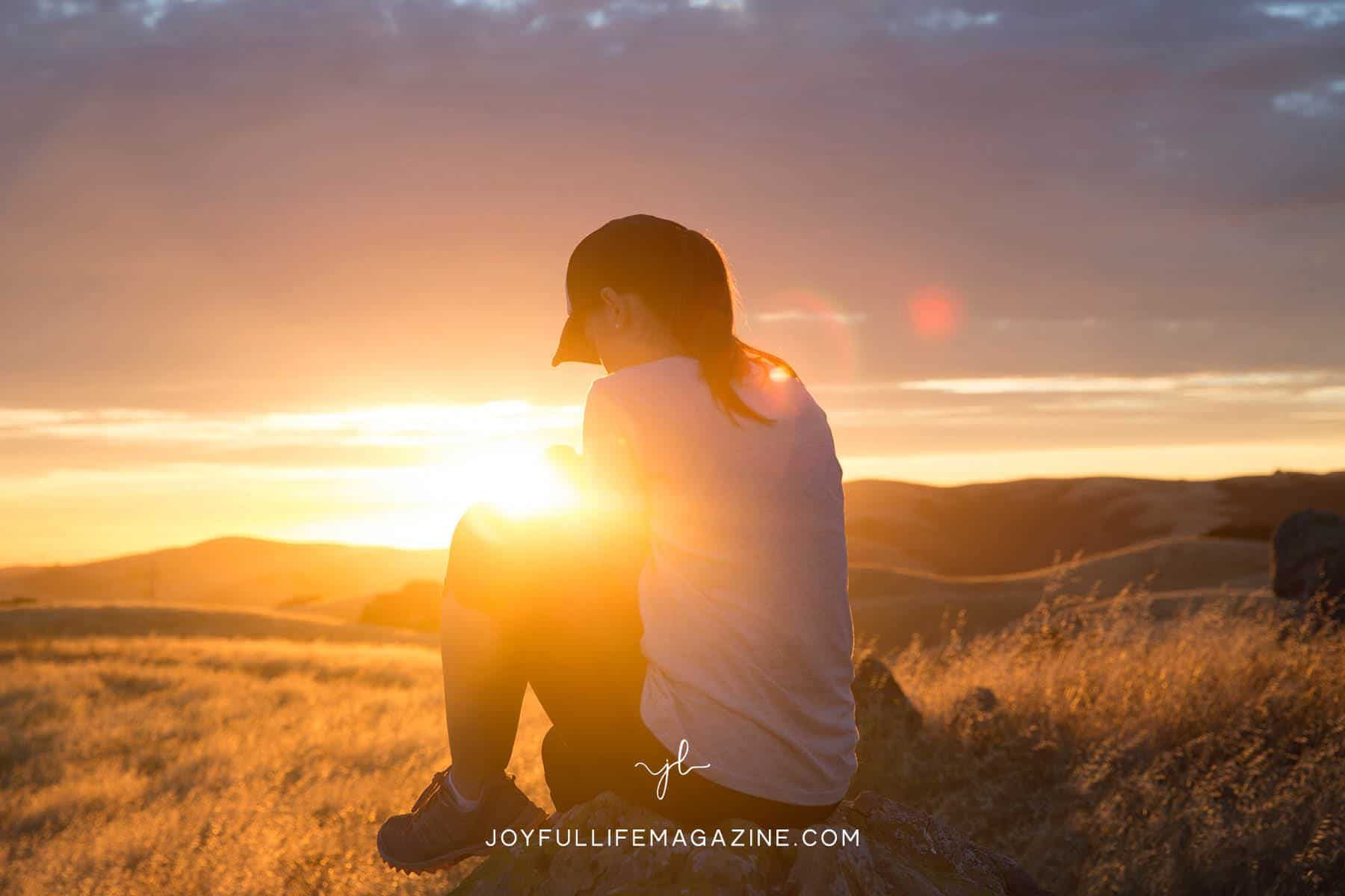 the lord's prayer - person sits in a field at sunrise and prays