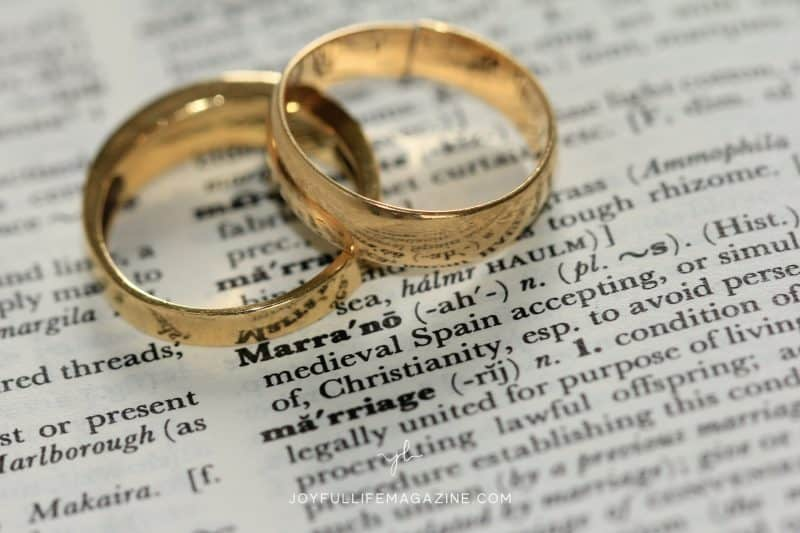 two wedding bands placed over the dictionary definition of marriage | common myths about marriage