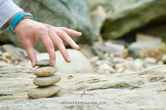 Hand stacking four stones