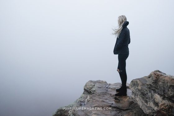 Girl dressed in all black standing on top of mountain surrounded by fog