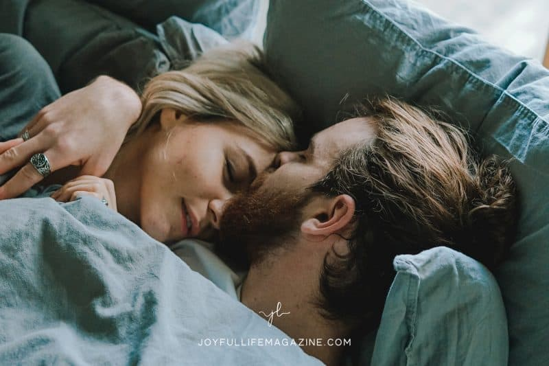 Husband and wife laying in bed, husband kissing wife's forehead