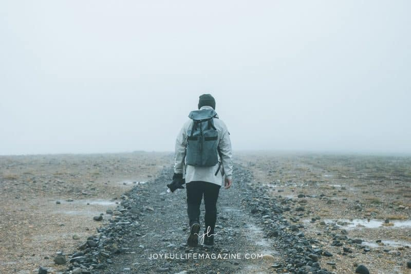 Person walking down a foggy path wearing a backpack.