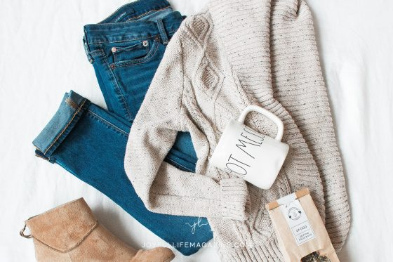 Flat lay of jeans, sweater, boots and mug