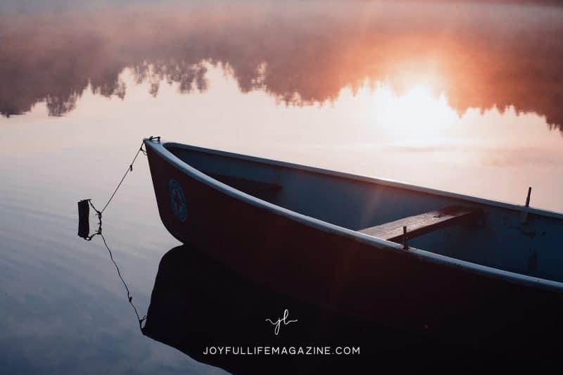 Canoe on still lake during sunset