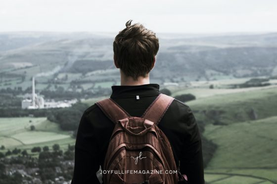 Young man overlooking a city with a backpack on his back