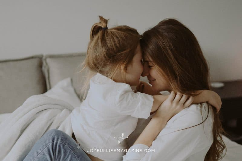 Mom and young daughter hugging with their foreheads pressed against each other.