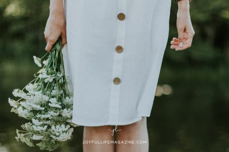 Woman in a dress from the waist down holding a bouquet of white flowers by her side