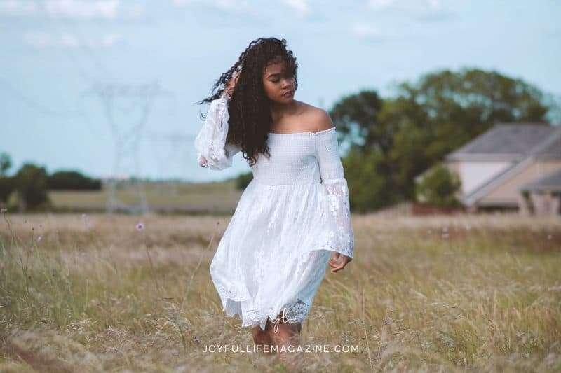 Woman in a white dress walking in a field
