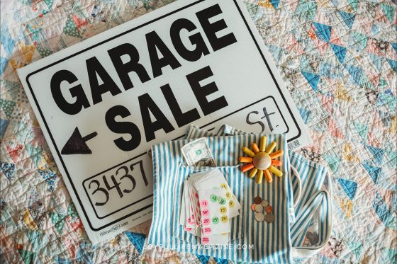 Garage Sale Sign and supplies on a flowery tablecloth