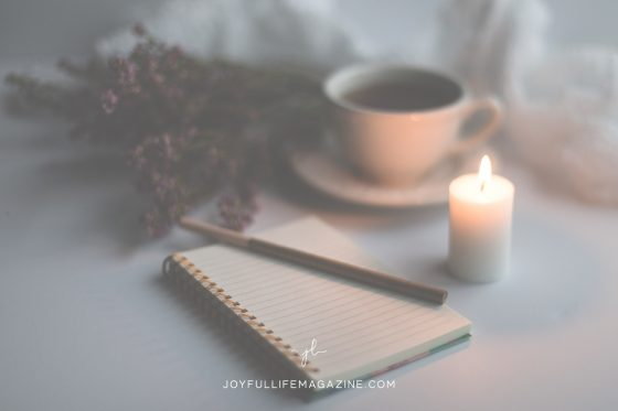 Coffee mug next to a lit candle and notepad with a pen