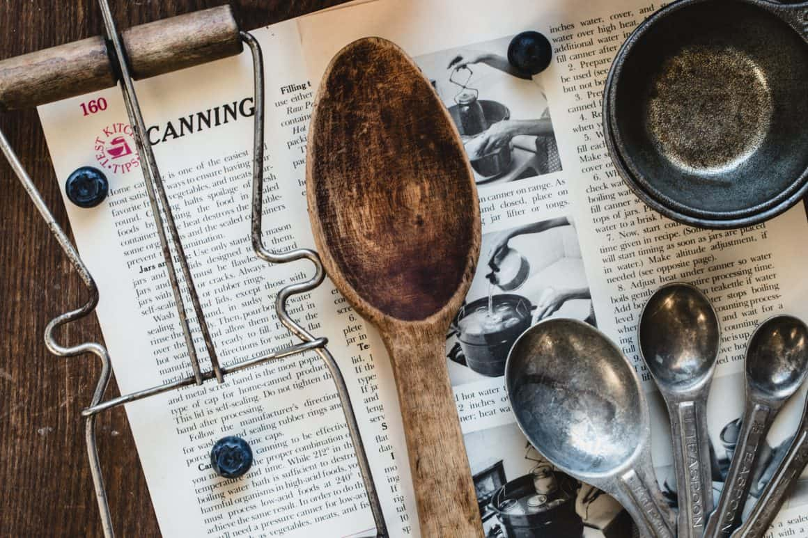 Wooden spoon and canning tool laying on canning instructions