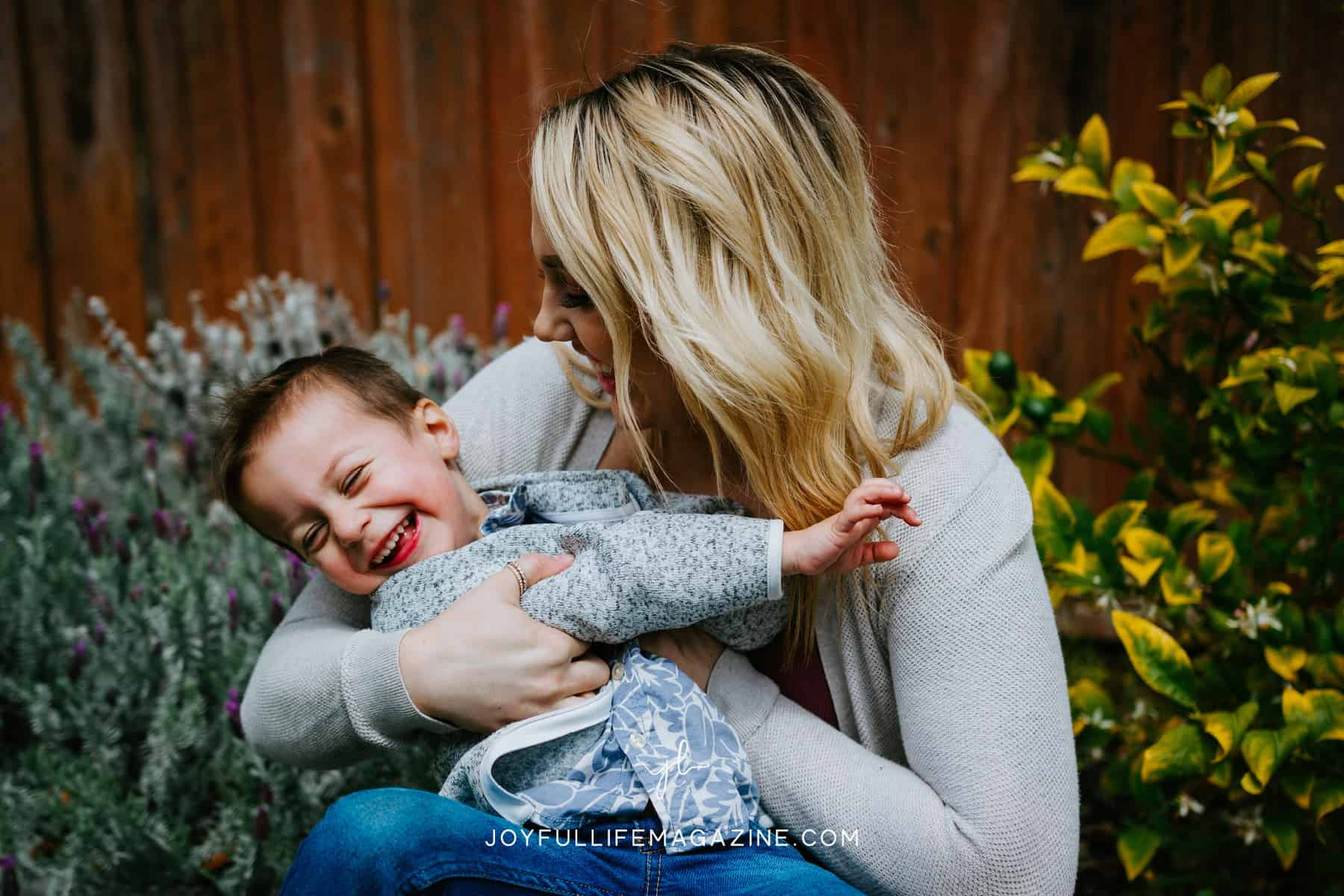 Mom holding toddler son and both laughing