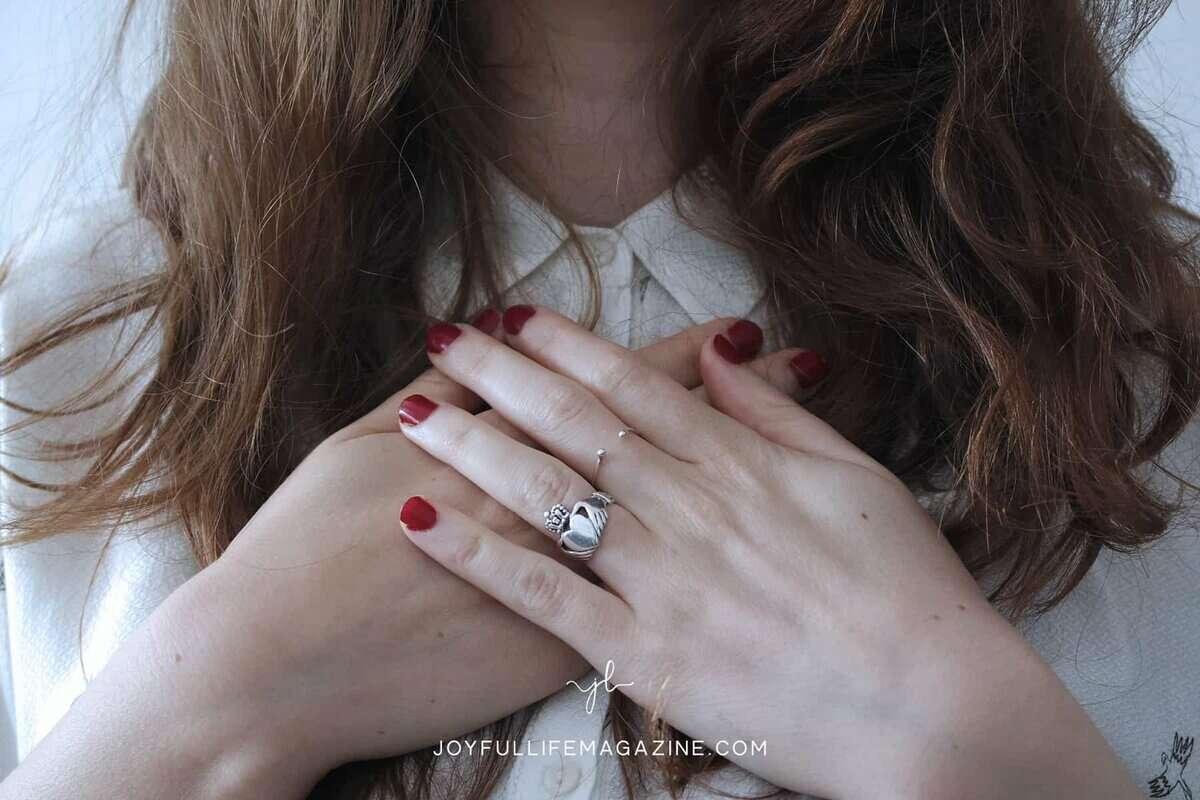 woman hands over heart