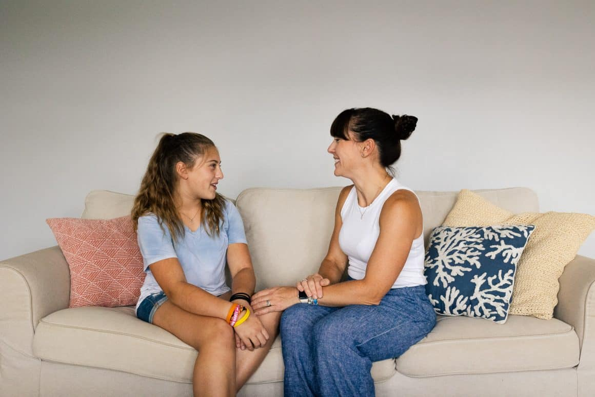 girl talking with mom on couch