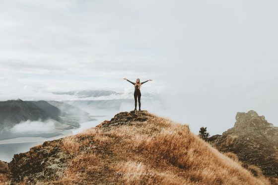 girl worshipping on top of a mountain