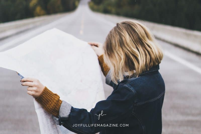 girl looking at map on road