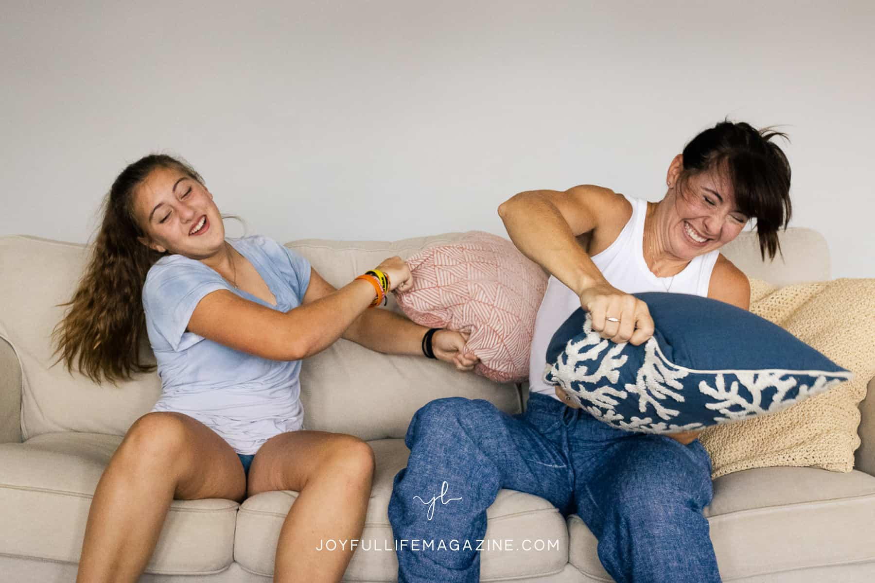 mom and daughter pillow fighting